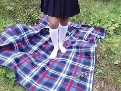 Schoolgirl in uniform shows legs...